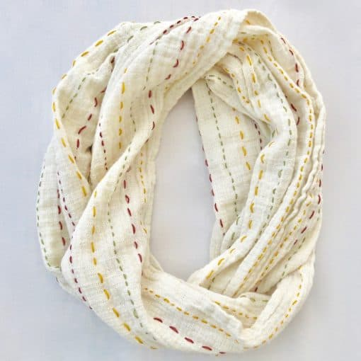 Soft cotton infinity scarf with colored threads stitched through.