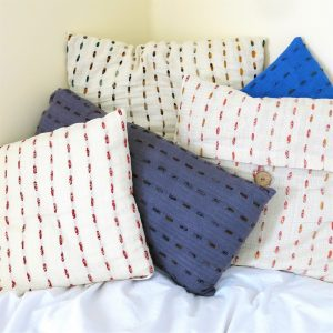 Fair trade fabric lumbar and other pillows. Hand stitching with recycled sari strips and naturally dyed.