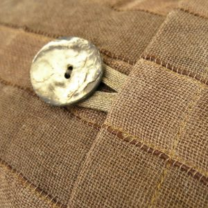 Sustainable fabric cushion covers with large coconut button.