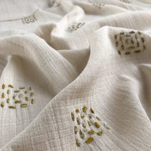 Sustainable fabric made with recycled sari ribbon hand stitched into soft natural cotton